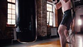 Um treinamento atl?tico do pugilista do homem com um saco de perfura??o no gym vídeos de arquivo
