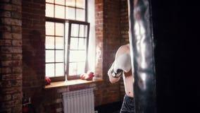 Um treinamento do pugilista do homem com um saco de perfuração vídeos de arquivo
