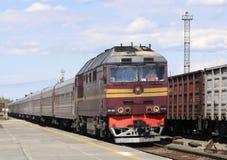 Um trem de passageiros com uma locomotiva diesel aproxima a plataforma da estação de trem, a cidade do ` de Pyt - Yakh, Rússia foto de stock royalty free