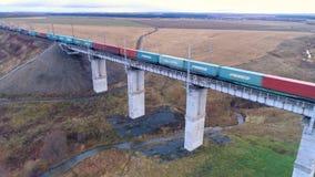 Um trem transporta contentores sobre uma ponte filme