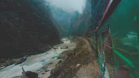 Um trem velho ou uma locomotiva estão viajando ao longo de uma estrada de ferro do estreito-calibre em um desfiladeiro estreito O vídeos de arquivo