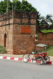 Um triciclo e uma parede da antiguidade Fotografia de Stock