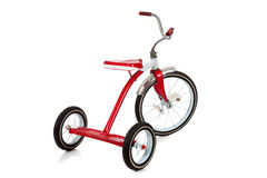 Um triciclo vermelho no branco Fotos de Stock Royalty Free