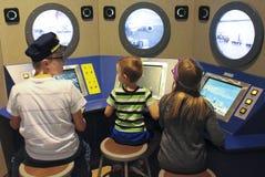 Um trio das crianças que têm o divertimento no museu do ` s das crianças da descoberta imagem de stock