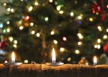 Um trio de velas do Natal em um registro de Aspen Imagem de Stock Royalty Free