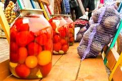 Um trole com tomates conservados, beterrabas em um malote na feira do outono foto de stock