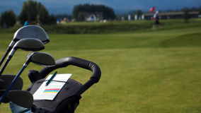 Um trole de golfe e um jogador de golfe no fundo Fotografia de Stock Royalty Free