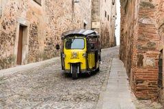 Um tuc amarelo do tuc faz uma rota do turista através da cidade velha de Caceres imagem de stock