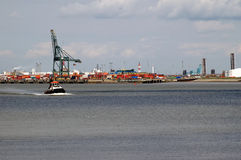 Um tugboat pequeno na frente de um porto enorme Fotos de Stock