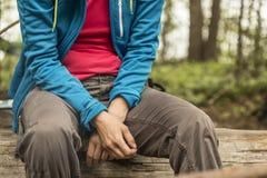 Um turista cansado está descansando o assento em um log, na floresta, em um fundo borrado das árvores e de um lago foto de stock royalty free