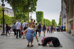 Um turista coloca moedas no copo de uma mulher que implora no passeio de Champs-Elysees Imagens de Stock Royalty Free