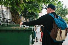 Um turista com uma trouxa e em um boné de beisebol na rua joga uma garrafa plástica em um recipiente com desperdício cuidado foto de stock