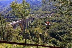 Um turista cruza sobre um teleférico longo sobre uma montanha e uma floresta através de Tiara River fotos de stock