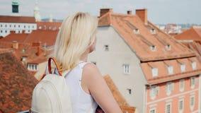 Um turista da jovem mulher está admirando a cidade europeia velha de uma altura Graz, Áustria Turismo em Europa tiro do steadicam filme