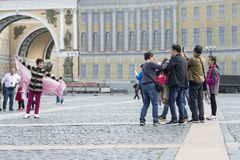 Um turista da mulher da aparência oriental que levanta para um grupo de compatriotas no quadrado do palácio de St Petersburg, Rús imagens de stock