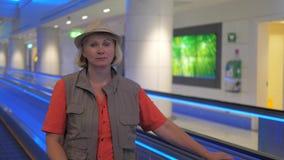 Um turista da mulher está estando em uma escada rolante movente no aeroporto video estoque