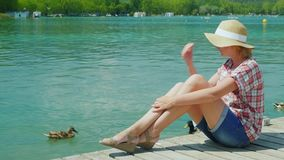 Um turista da mulher que aprecia férias no lago onde os patos nadam Recurso em Spain video estoque