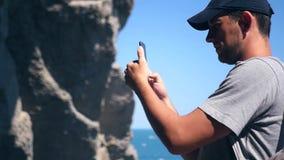 Um turista em um tampão faz uma foto de um penhasco bonito perto do mar HD, 1920x1080 Movimento lento video estoque