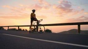 Um turista em uma bicicleta admira o por do sol da parte superior da montanha filme