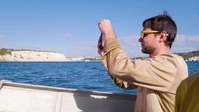 Um turista em uma camiseta bege nada em uma lancha no mar e toma uma foto no telefone Indivíduo novo, turismo, curso vídeos de arquivo