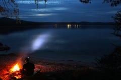 Um turista está sentando-se por uma fogueira na noite foto de stock royalty free