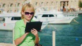 Um turista fêmea aprecia a tabuleta contra o contexto da baía com iate vídeos de arquivo