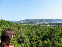 Um turista fêmea novo que admira a vista de Neddy e Rocky Harbour, Norris Point, e baía de Bonne imagens de stock royalty free