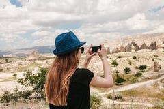 Um turista faz uma foto no telefone na memória de uma vista bonita dos montes em Cappadocia em Turquia Curso, turismo foto de stock royalty free