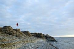 Um turista fotografa na costa pelas formações de pedra Imagens de Stock