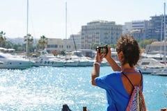 Um turista fotografa o mar na Creta fotografia de stock royalty free