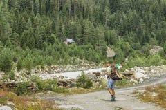 Um turista masculino novo com uma trouxa está andando ao longo de uma estrada nas montanhas em Svaneti, Geórgia foto de stock royalty free