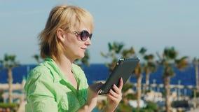 Um turista nos óculos de sol aprecia a tabuleta em um fundo de uma paisagem tropical vídeos de arquivo