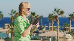 Um turista nos óculos de sol aprecia a tabuleta em um fundo de uma paisagem tropical filme