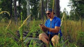 Um turista nos óculos de sol e em um boné de beisebol na floresta em um dia ensolarado senta-se em uma árvore caída e comunica-se vídeos de arquivo