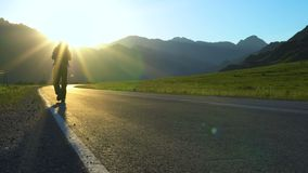 Um turista novo com uma trouxa vai na estrada em uma área montanhosa filme