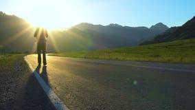 Um turista novo com uma trouxa vai na estrada em uma área montanhosa video estoque