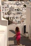 Um turista pequeno bonito atravessa para uma caminhada as ruas de Santorini imagem de stock royalty free