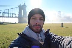 Um turista toma um selfie na frente de uma ponte bonita imagens de stock royalty free