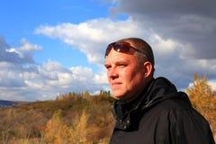 Um turista 35-40-year-old em um revestimento preto e em óculos de sol olha Fotografia de Stock Royalty Free