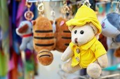 Um urso de peluche pequeno em um revestimento amarelo e em um chapéu foto de stock
