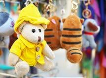 Um urso de peluche pequeno em um revestimento amarelo e em um chapéu imagem de stock