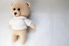 Um urso pequeno bonito bonito caseiro feito malha em uma camiseta branca com olhos roxos, um brinquedo macio amarrado com as gran fotografia de stock
