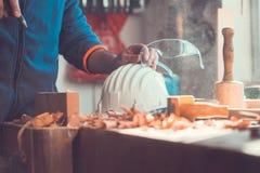 Um uso do carpinteiro uma bomba de ar limpar a parte de madeira, bocais de ar atira à disposição, poeira no ar Imagens de Stock