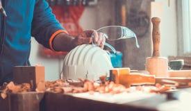 Um uso do carpinteiro uma bomba de ar limpar a parte de madeira, bocais de ar atira à disposição, poeira no ar Fotografia de Stock