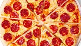 Um vídeo do fundo movente corta a pizza de pepperoni footage video estoque
