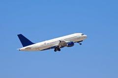 Um vôo do plano de jato em um céu azul Fotos de Stock