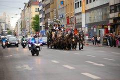 Um vagão da cerveja com escolta policial faz sua maneira com o tráfego Foto de Stock Royalty Free