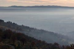 Um vale encheu-se pela névoa no por do sol, com uma estrada e as árvores no Fotografia de Stock