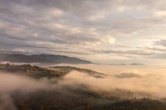 Um vale no outono encheu-se pela névoa no por do sol, com os montes emergentes Fotografia de Stock Royalty Free