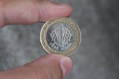 Um valor da moeda 1 lira turca entre os dedos da mão Foto de Stock Royalty Free